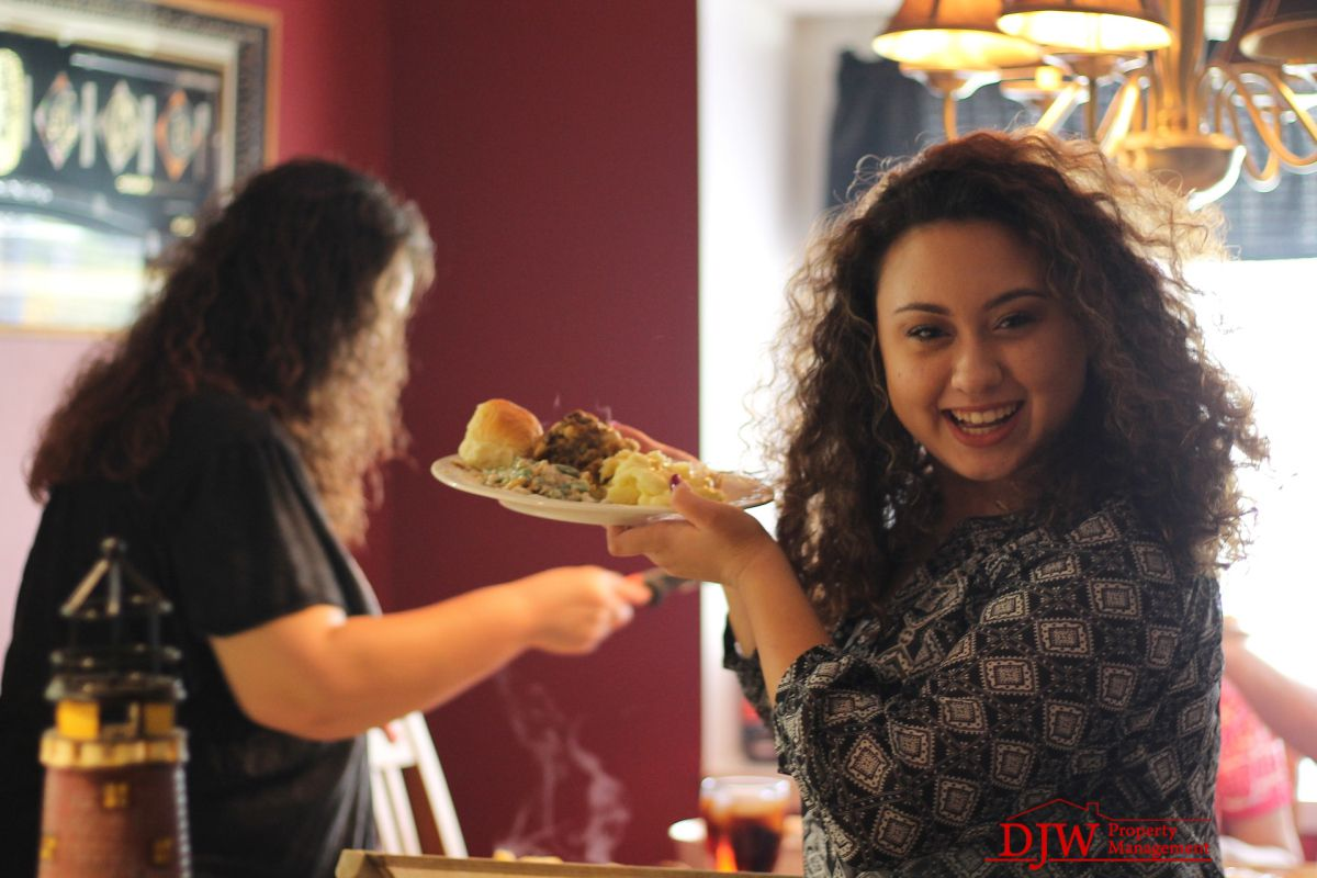 A girl with curly hair holding up a dinner plate full of Thanksgiving food, while her family is gathered around the table in her small rental.
