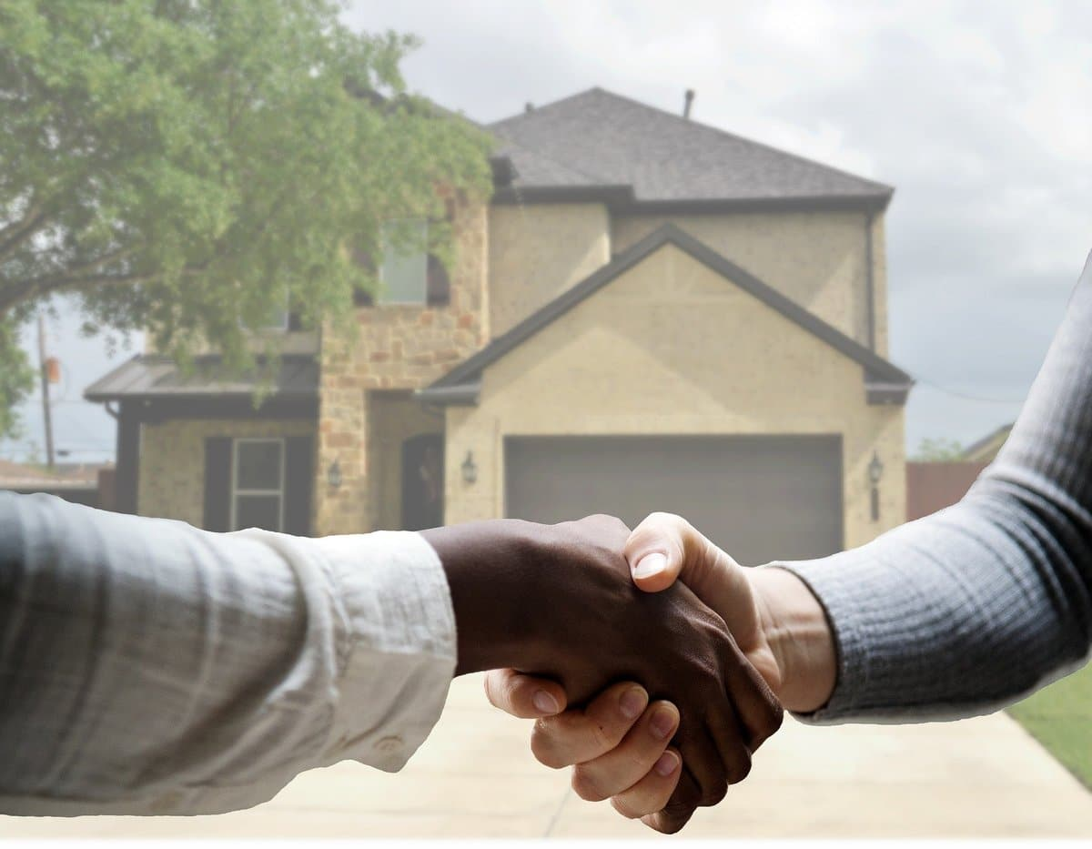 Firm handshake in front of a two-story home; leafy tree in the upper left corner.
