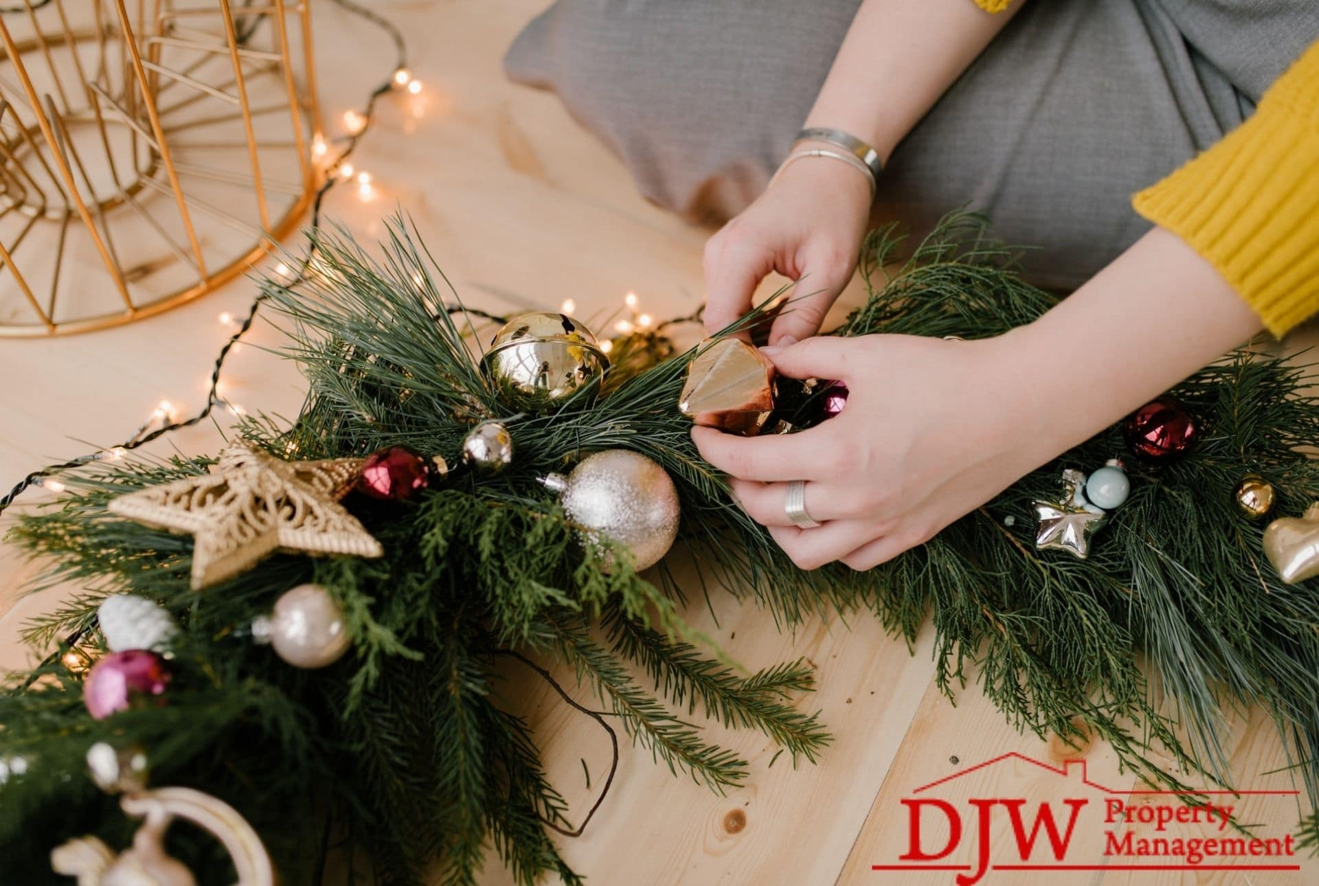 A woman makes a wreath from garland, twinkle lights, and tree ornaments.