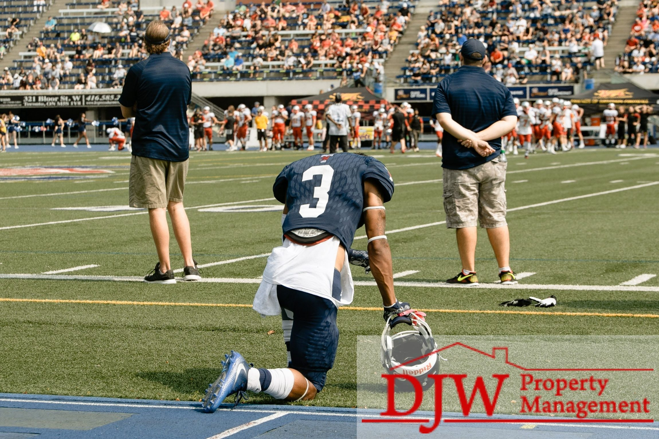 Football player taking a knee on the sidelines.
